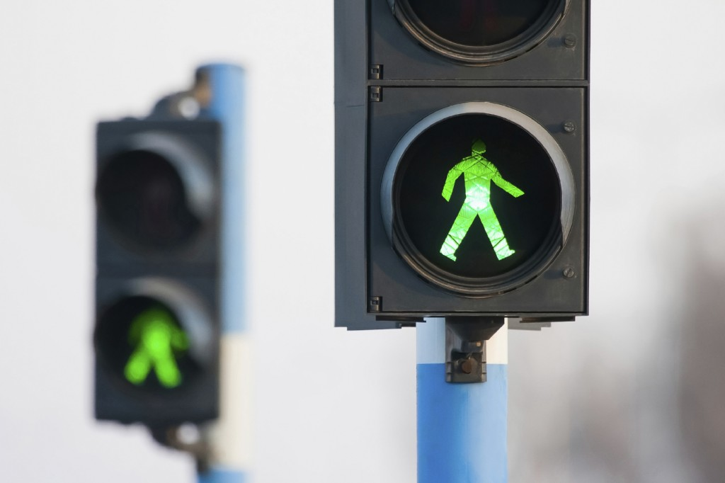 Green lights for pedestrians on two semaphores in traffic.
